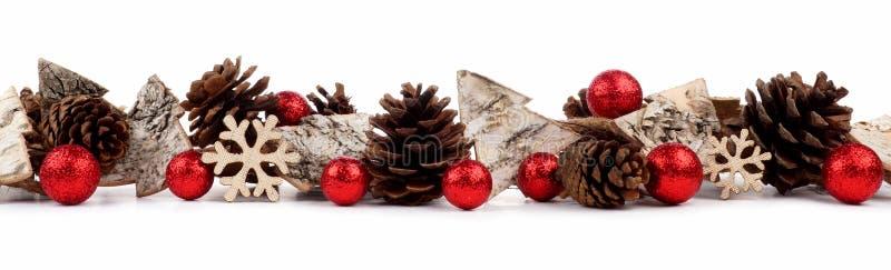 Frontera de la Navidad con los ornamentos del árbol, las chucherías rústicas y los conos de madera del pino aislados sobre blanco fotografía de archivo libre de regalías