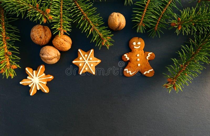 Frontera de la Navidad hecha de rama de la picea, de wallnuts y de la galleta del hombre de pan de jengibre foto de archivo