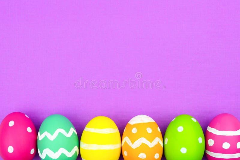 Frontera de la parte inferior del huevo de Pascua sobre fondo de papel púrpura fotografía de archivo libre de regalías