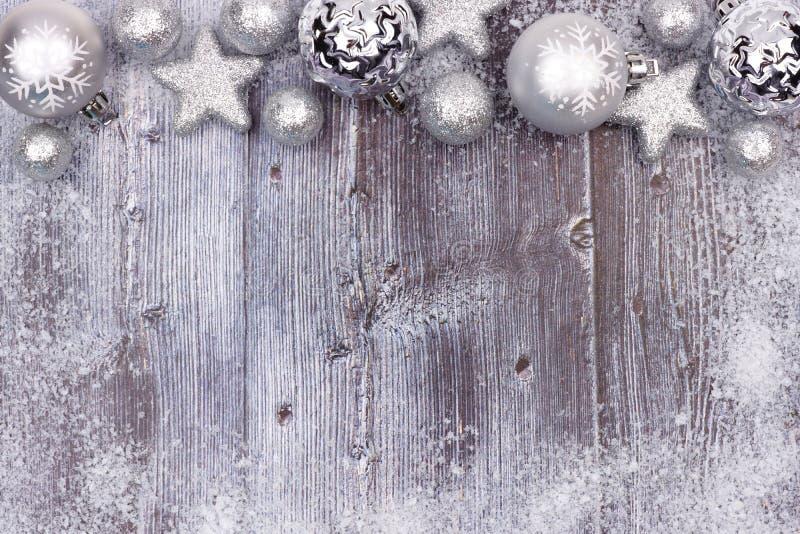 Frontera de plata del top del ornamento de la Navidad con el marco de la nieve en la madera imágenes de archivo libres de regalías
