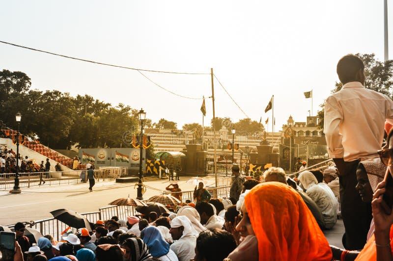 FRONTERA DE WAGHA, AMRITSAR, PUNJAB, LA INDIA - JUNIO DE 2017 La gente recolectó en la baja de la ceremonia de las banderas Su un fotografía de archivo