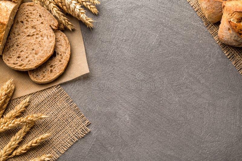 Frontera del pan en la tabla de piedra con el fondo del espacio de la copia Panadería, el cocinar y concepto del colmado foto de archivo