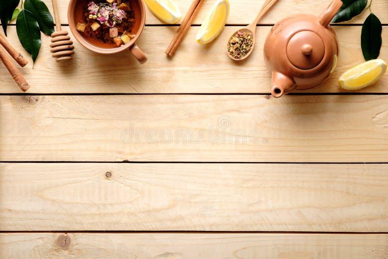 Frontera o marco superior de la taza de infusión de hierbas, tetera, cuchara del té secado, limón, canela en la tabla de madera V foto de archivo libre de regalías