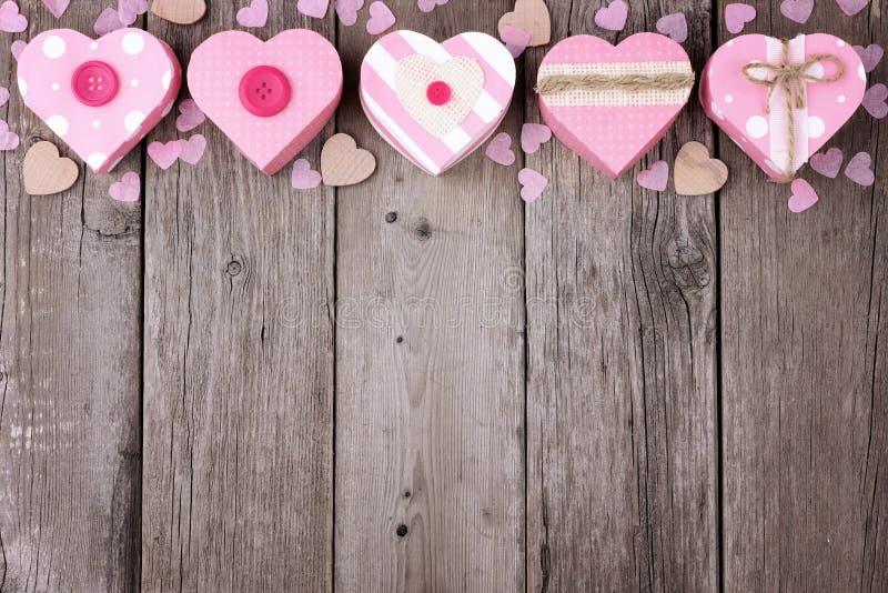 Frontera rústica del top del día de tarjetas del día de San Valentín con las cajas de regalo en forma de corazón rosadas fotos de archivo