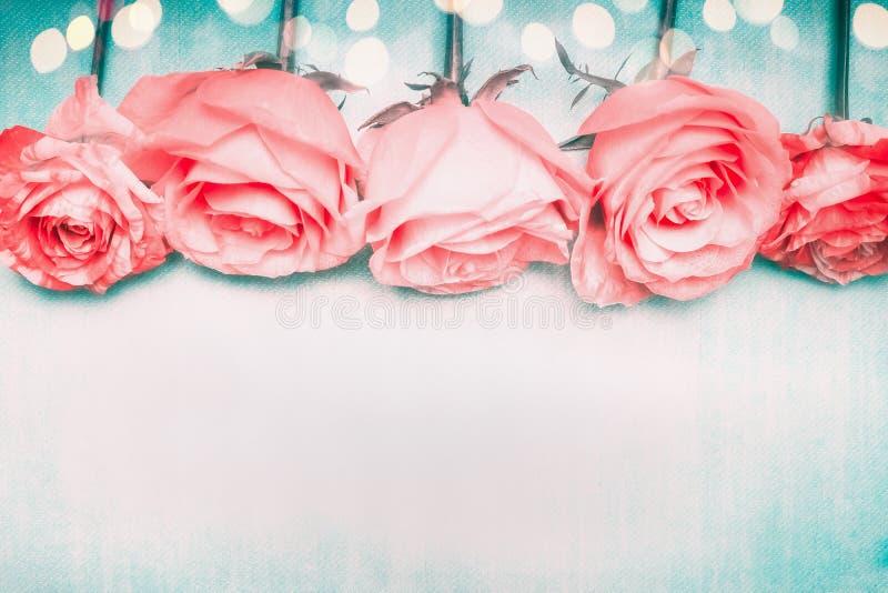 Frontera romántica hermosa de las rosas en fondo azul con el bokeh en color en colores pastel fotografía de archivo libre de regalías