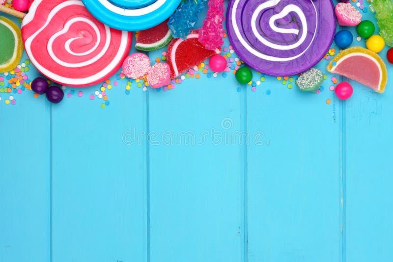Frontera superior de caramelos clasificados coloridos contra la madera azul foto de archivo