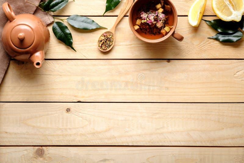 Frontera superior de la taza de infusión de hierbas, tetera, hojas verdes, cuchara del té secado, limón en fondo de madera Visión fotografía de archivo libre de regalías