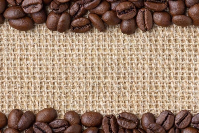 Frontière de café Haricots au-dessus de fond de toile de jute photographie stock libre de droits