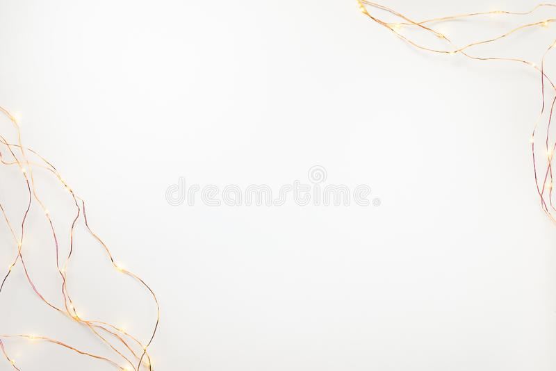 Frontière de guirlande de lumières de Noël au-dessus du fond blanc Configuration plate, l'espace de copie photos stock