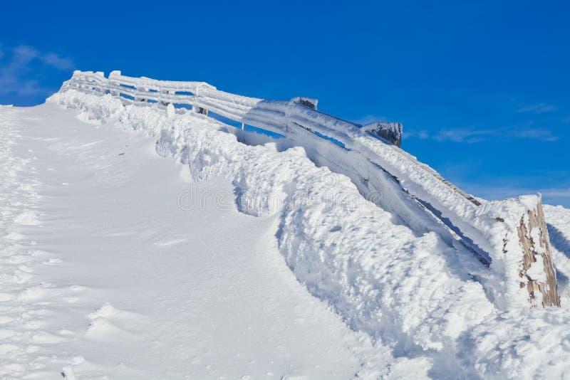 Frontière de sécurité en bois couverte dans la neige photo stock