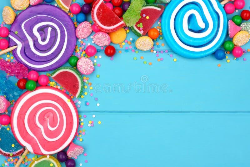 Frontière faisante le coin des sucreries assorties colorées contre le bois bleu photo libre de droits