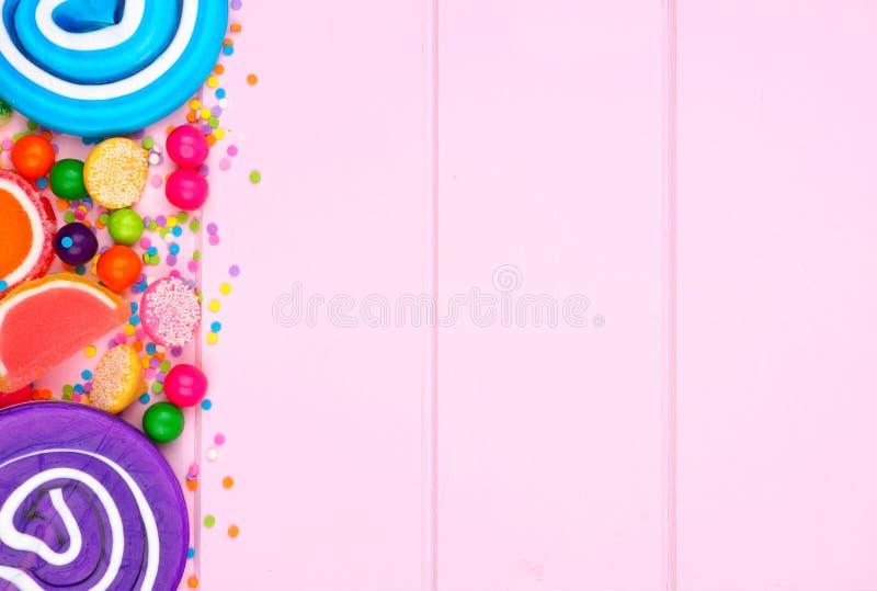 Frontière latérale des sucreries colorées assorties contre le bois rose photographie stock