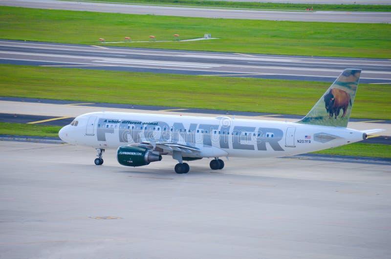 Frontier Airlines hyvlar på flygplatsgrova asfaltbeläggningen royaltyfri foto