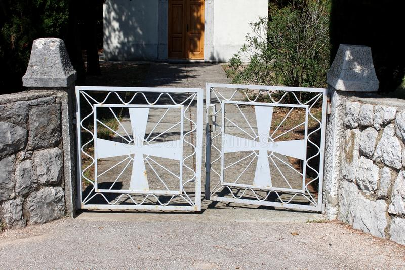 Frontowego wejścia metalu drzwi w stylu krzyż i światło emanuje od centrum otaczającego z tradycyjną kamienną ścianą prowadzi zdjęcie royalty free