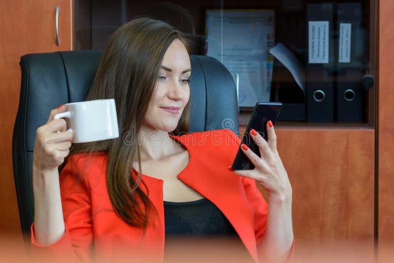 Frontowego widoku portret młoda kobieta w czerwonym garnituru obsiadaniu w rzemiennego krzesła pić kawowy i używać smartphone zdjęcia stock