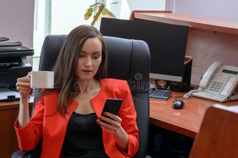 Frontowego widoku portret młoda kobieta w czerwonym garnituru obsiadaniu w rzemiennego krzesła pić kawowy i używać smartphone fotografia stock