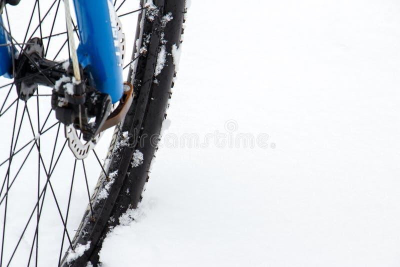 Frontowi koła rower górski zostają w śniegu i podążają ścieżkę Śnieżni płatki unosi się na ciemnych dróg oponach zdjęcia royalty free