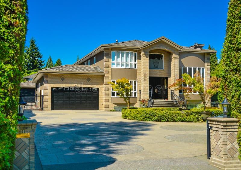 Frontowy jard luksusowy rodzina dom z brukującym podjazdem na niebieskiego nieba tle obrazy stock
