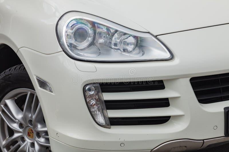 Frontowy reflektoru widok Porsche Cayenne 957 2007 w białym kolorze po czyścić przed sprzedażą w letnim dniu na parking zdjęcie royalty free