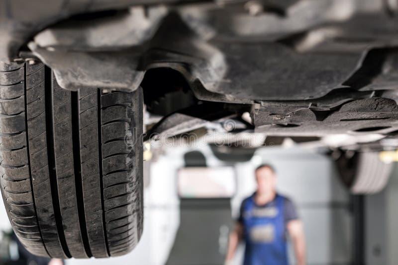 Frontowy samochodowy zawieszenie garażu mechanik podnosił samochód na dźwignięciu obraz stock