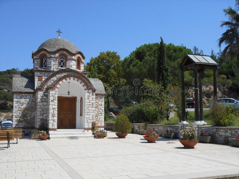 Frontowy widok biały, brown kościół i Agios Nikolaos Anastasia przy połowu schronieniem Olympiada, Halkidiki i belfr, obraz royalty free