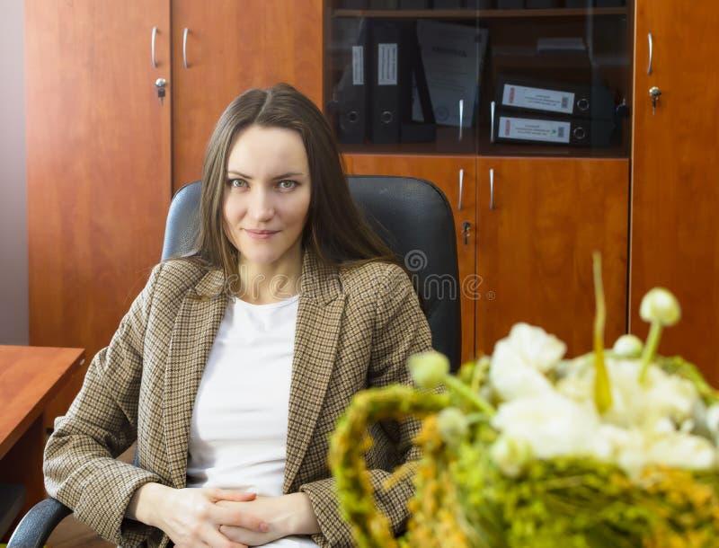 Frontowy widok biznesowej kobiety obsiadanie stołem w biurowej i patrzeje kamerze zdjęcie stock