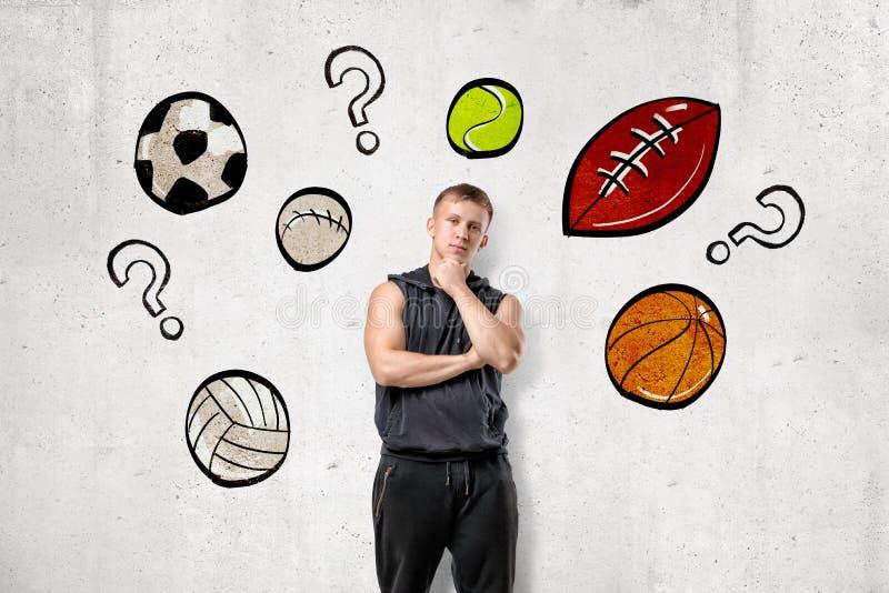 Frontowy widok młody człowiek w sleeveless hoody pozycji z ręki nacierania podbródkiem przy ścianą z rysunkami różny sport ilustracji