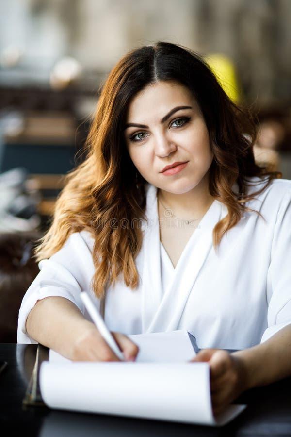 Frontowy widok M?oda kobieta siedzi w kawiarni przy sto?em, mienia pi?ro, czyta dokumenty Bizneswoman podpisuje kontrakt Rozpoczę obrazy royalty free