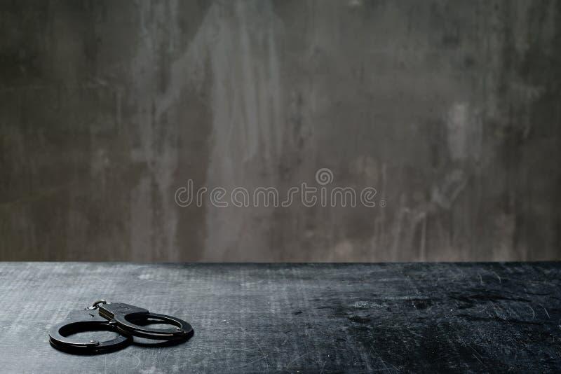 Frontowy widok metali kajdanki na stole w przesłuchanie pokoju fotografia royalty free