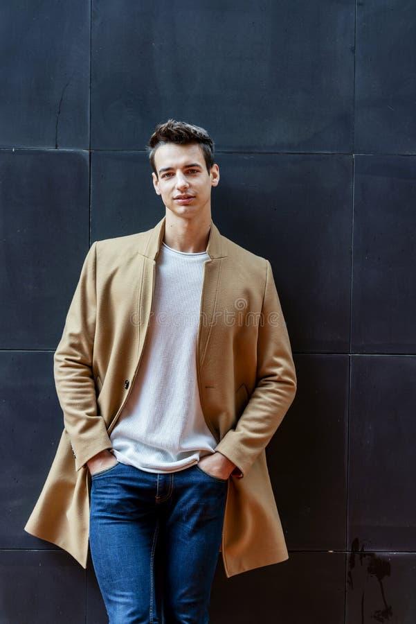 Frontowy widok modna młody człowiek pozycja przeciw czerni ścianie podczas gdy patrzejący kamerę outdoors w ulicie zdjęcia royalty free