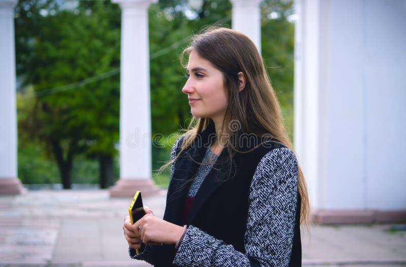 Frontowy widok mody kobieta chodzi mądrze telefon na miasto ulicie i używa zdjęcia royalty free