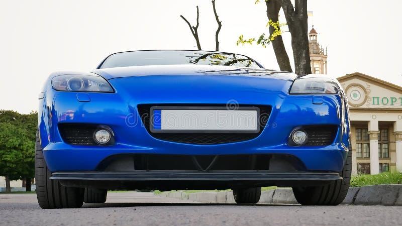 Frontowy widok Nowy Czysty Błękitny sportowy samochód Parkujący na ulicie obraz stock
