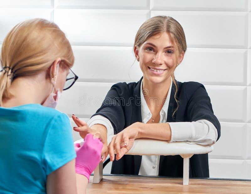 Frontowy widok patrzeje kamerę kobieta podczas gdy odbiorczy śliczny manicure zdjęcie royalty free