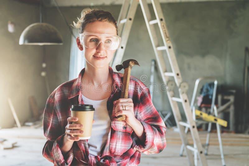 Frontowy widok Portret szczęśliwy młody żeński pracownik budowlany, cieśla, repairman pozycja w warsztacie obraz stock