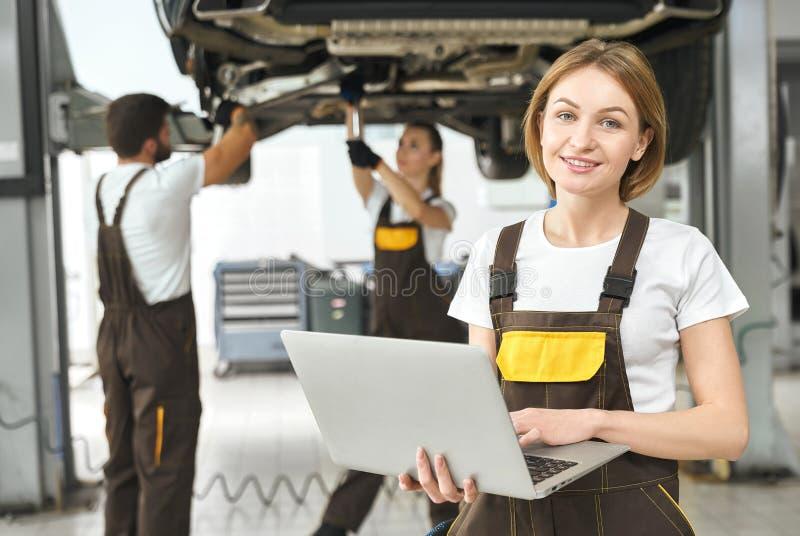 Frontowy widok pracuje przy samochód usługą atrakcyjna kobieta obrazy stock