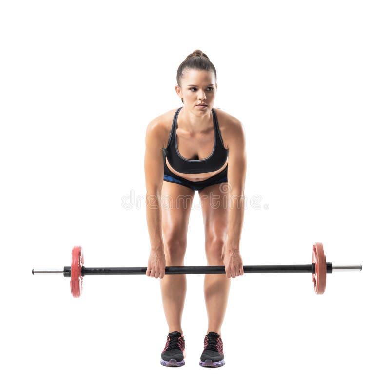 Frontowy widok przegięta żeńska atleta robi nieżywemu dźwignięcia ćwiczeniu z barbell patrzeje daleko od fotografia stock