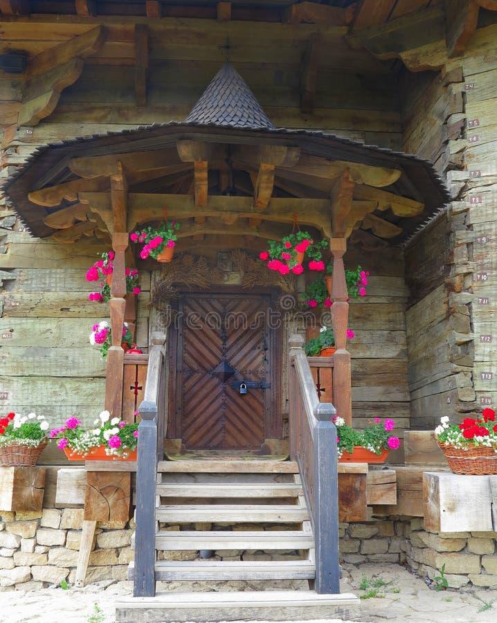 Frontowy widok rocznika dzwi wejściowy drewniany ganeczek z kwiatami zdjęcie royalty free