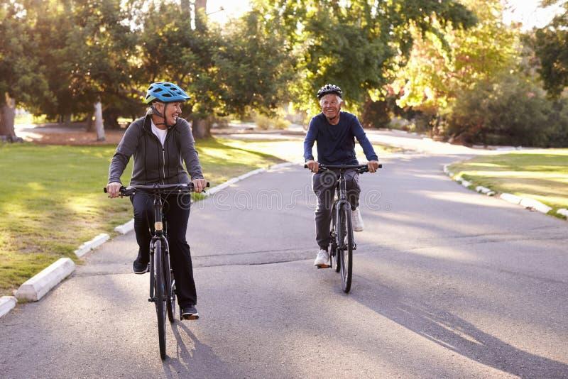 Frontowy widok Starszy pary kolarstwo Przez parka Wpólnie zdjęcie royalty free