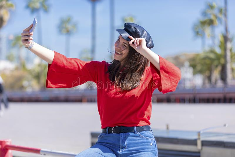 Frontowy widok uśmiechnięty młodej kobiety przypadkowej odzieży obsiadanie na kruszcowym ogrodzeniu podczas gdy brać selfie w jas fotografia stock