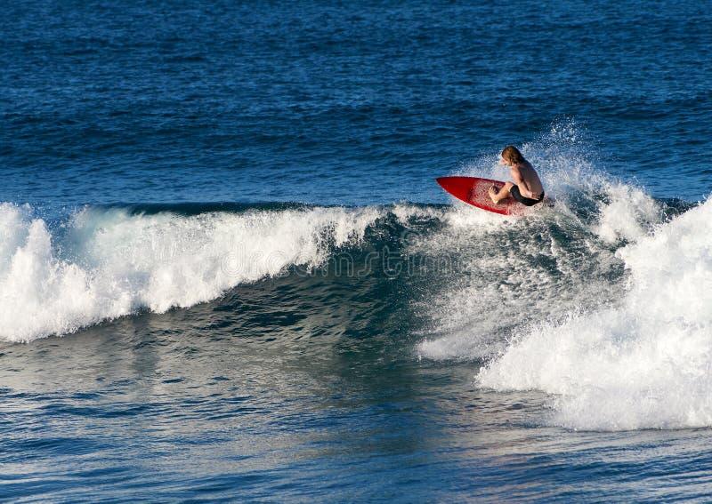 Frontside-aus-dlippe auf rotem Surfbrett stockfotografie