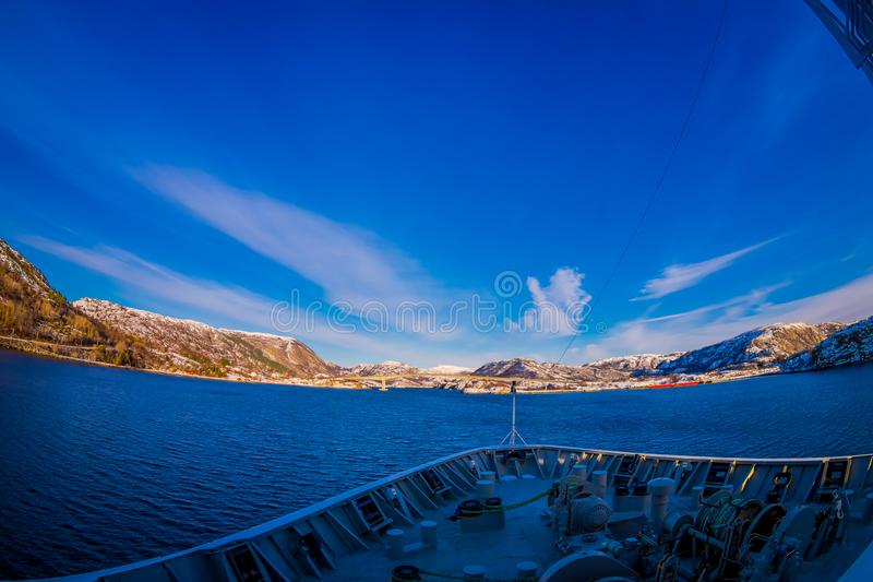 Frontside view from hurtigruten Ship cruise, with a gorgeous coast with buildings in the horizont. In a blue sky in Norway stock photo
