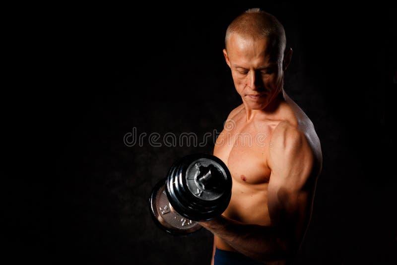 Frontview do halterofilista forte com o relevo muscular claro que levanta o peso pesado no gym Estilo de vida do esporte Gym regu foto de stock royalty free