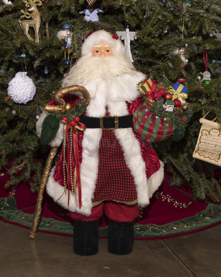 Frontview of small Santa Claus in front of a Christmas tree. Frontview of a small Santa Claus standing in front of a Christmas tree with a gold staff in right stock photography