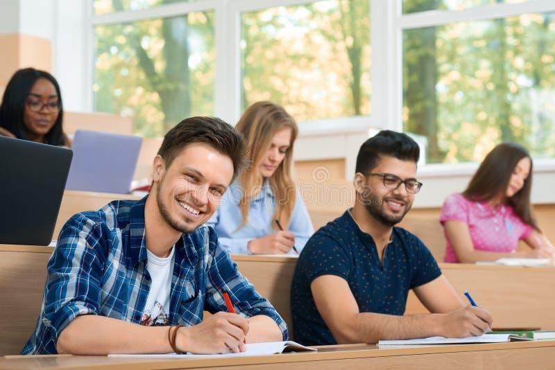 Frontview von Studuing während der Lektionsstudenten, die Kamera betrachten stockbild