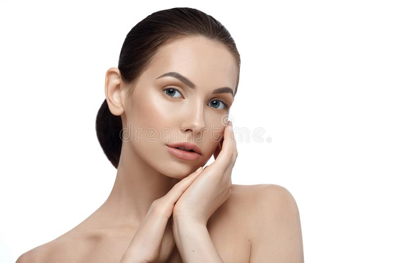 Frontview of young woman with pretty cute face posing touching her face. stock photos