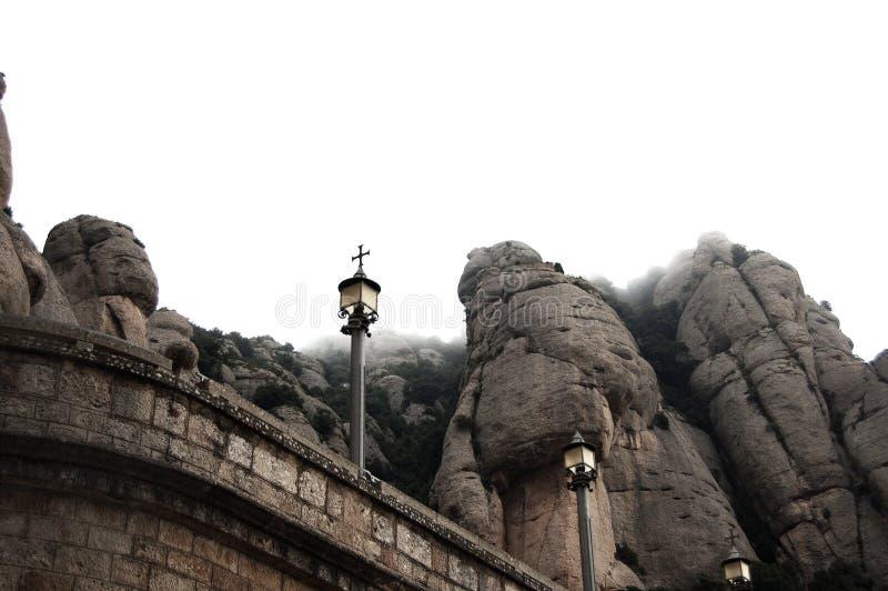 Froschperspektive einer Postenlampe bis zum Hügel nahe dem Berg im Nebel bei Montserrat lizenzfreies stockbild