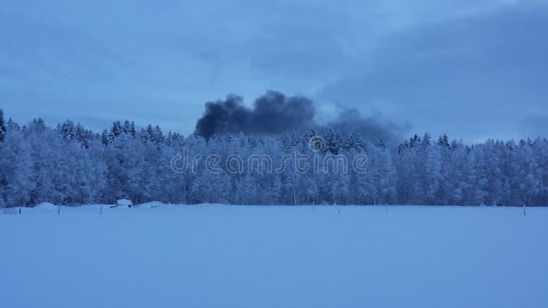 Frost cubrió el bosque y el campo nevoso con humo oscuro del fuego en el fondo debido al edificio ardiente imagenes de archivo