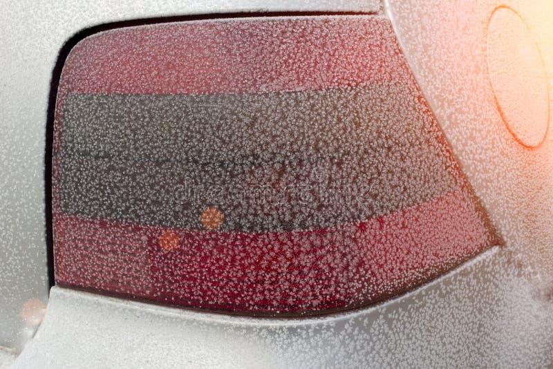 Frost en el auto posterior de la linterna y del sol del coche foto de archivo