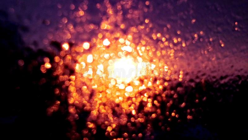 Frost on the glass. The bright frost, frost on the glass, bright light, landscape, purple, orange, yellow, white, red light royalty free stock photo