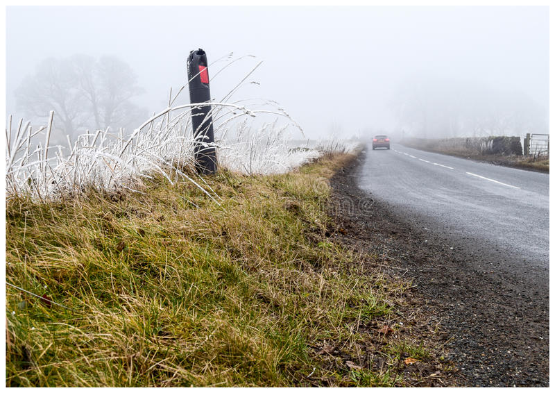 Frost hit grass verge. Roadside grass verge with frost at the top of the grass caused by freezing fog. With car in distance royalty free stock images
